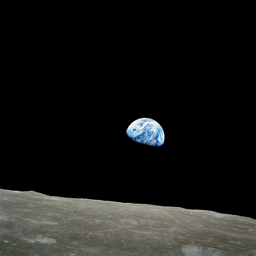 Photo de la Terre partiellement dans l'ombre, avec au premier plan la surface lunaire, à la manière d'un lever de soleil.