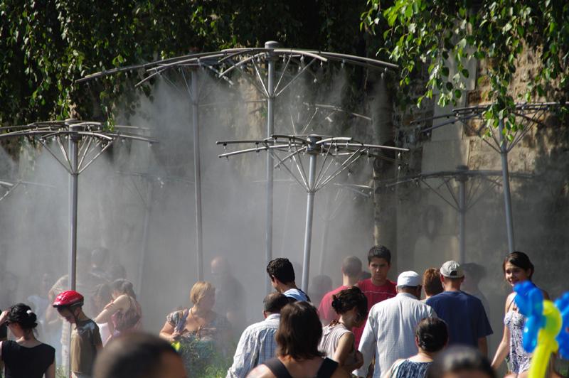 Photographie de la foule sous de brumisateurs