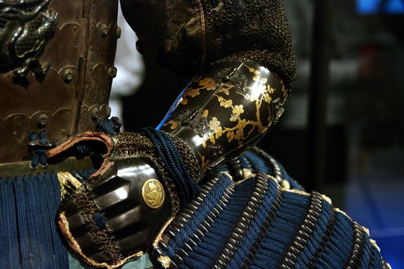 Détail de l'armure d'un samouraï : brassard noir laqué et incrustation dorée de forme végétale